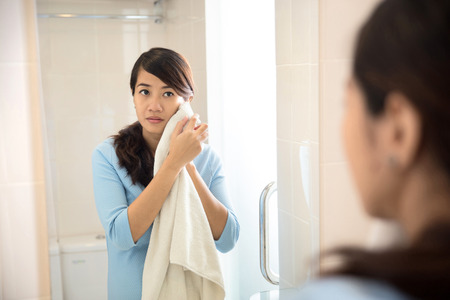 A portrait of a Beautiful asian woman wiping her face with towel, looking at mirror