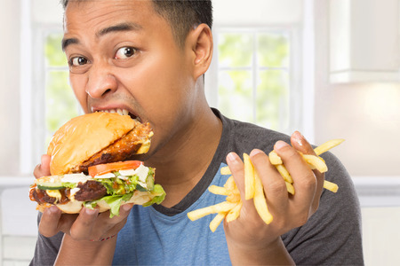 deliciously: A portrait of a young man bite his big burger deliciously while the other hand holding chips Stock Photo