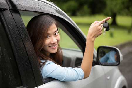 A portrait of a young asian woman inside a car, hold the key out from the window