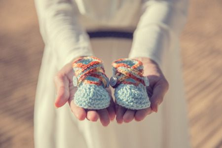 motherly: close up portrait of woman hands holding a pair of baby shoes Stock Photo