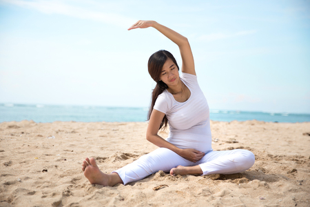 embarazada: Un retrato de una mujer asi�tica embarazada que hace yoga en la orilla del mar Foto de archivo