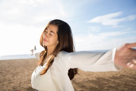 closing time: A portrait of an Asian woman enjoying her time in the beach, closing her eyes and arms open wide