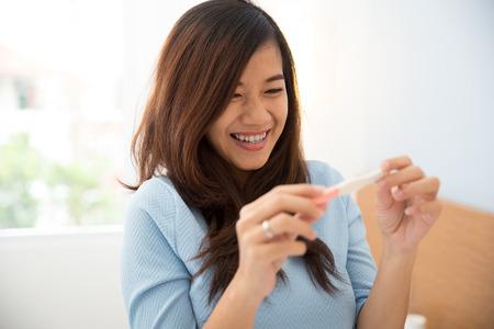 test de grossesse: Portrait de jeune femme excitée asiatique avec un testpack dans sa main, un sourire heureux Banque d'images