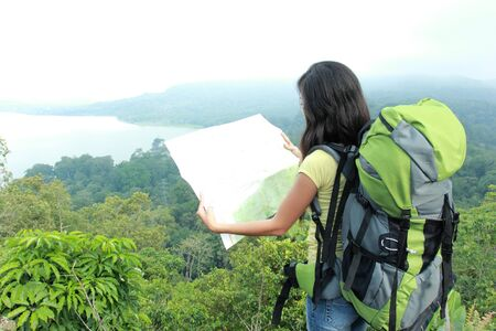 knapsacks: A portrait of a young asian woman travel backpacking, outdoor looking at map Stock Photo