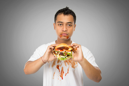 glut: A portrait of a young asian in silent with a big burger on his hands