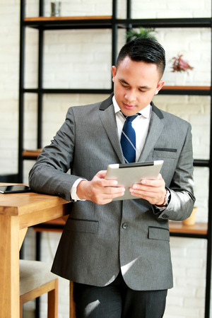 lean back: portrait of young businessman reading news on tablet Stock Photo