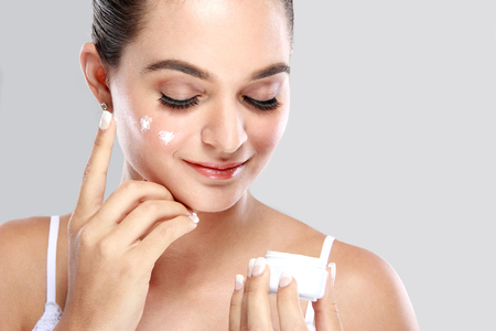 schoonheid: portret van mooie vrouw die wat room op haar gezicht voor huidverzorging Stockfoto