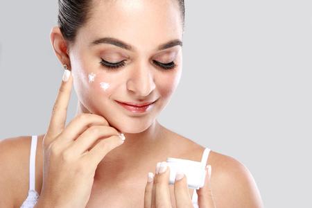 mujer maquillandose: retrato de la hermosa mujer de aplicar un poco de crema en la cara de cuidado de la piel Foto de archivo
