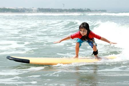 portret van de kleine jongen leren om te surfen op de oceaan