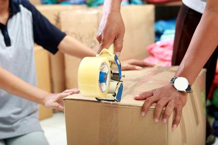 carton: retrato de trabajador con cinta para embalar el producto en una caja en la fábrica textil