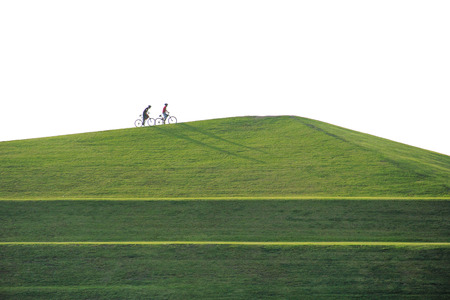 open country: pportrait of beautiful hill landscape with two people riding bicycle