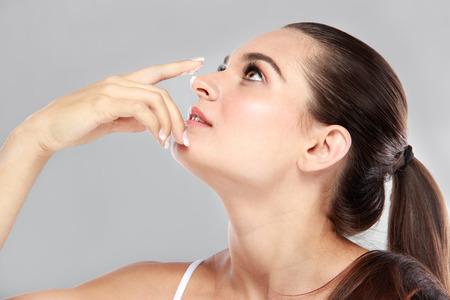 nariz: vista lateral de la hermosa joven que aplicar un poco de crema facial en su nariz