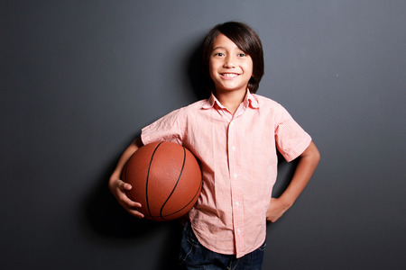good looking boy: portrait of good looking boy smiling while holding a basketball with dark background Stock Photo