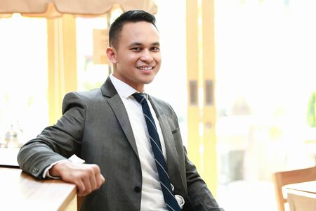 smiling businessman: young businessman smiling while sitting and lean back at table