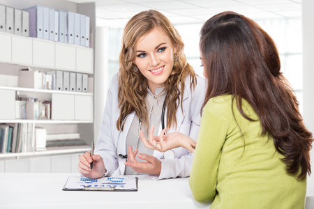 doctor consultation: A portrait of a Doctor with female patient. Friendly, Happy Doctor with Stethoscope Giving Advice to Patient in Clinic