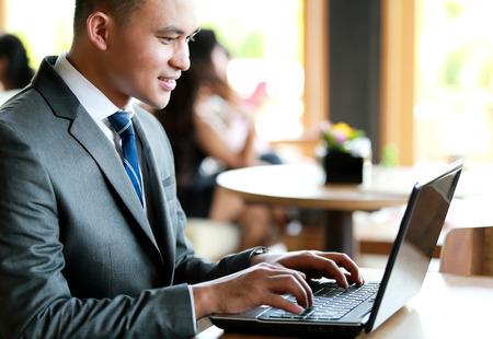 ejecutivos: retrato de joven empresario de trabajo con ordenador portátil en cafetaria Foto de archivo