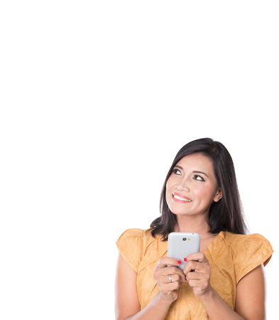 girl looking up: A portrait of a pretty Asian Woman, text on her cellphone and looking up to copyspace Stock Photo