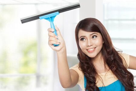 dry: A portrait of a Beautiful young asian women doing domestic chores using glass cleaning wiper