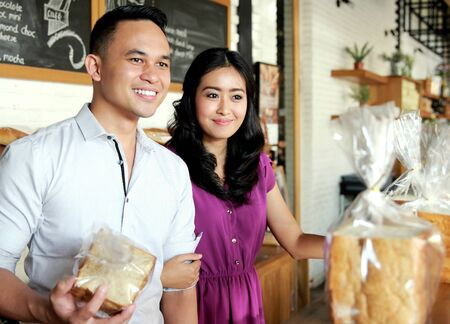 couple dating: amazing young couple smiling while shopping at bakery shop