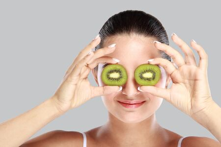 eye mask: portrait of young woman holding slices of kiwi in front of her eye for make up mask