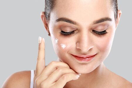 young add: close up portrait of beautiful young woman smiling while applying some facial cream on her cheek
