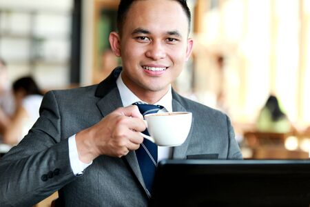 drink coffee: portrait of handsome businessman having a coffee break Stock Photo