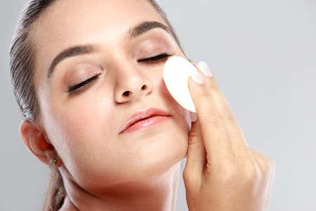 powder puff: close up portrait of beautiful woman applying some powder using powder puff with closed eyes