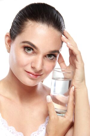 vaso con agua: retrato de la bella modelo caucásica posando con un vaso de agua aislado en blanco Foto de archivo