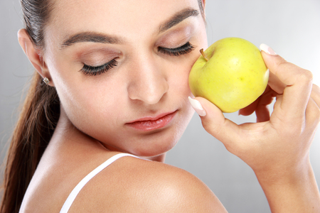 close up eyes: close up portrait of beautiful woman holding a fresh apple with eyes closed