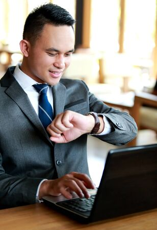 idea comfortable: portrait of young businessman looking at his watches