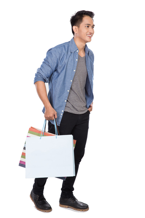 A portrait of young asian man walking and holding shopping bags, full body Foto de archivo