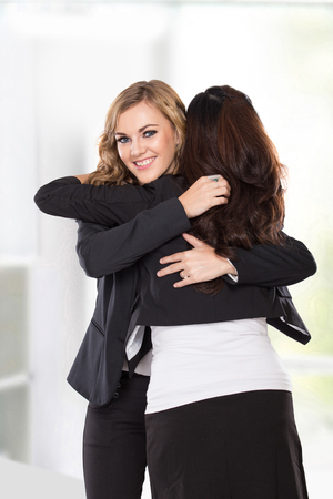 man woman hugging: A portrait of a two young businesswoman have a reconciliation, isolated