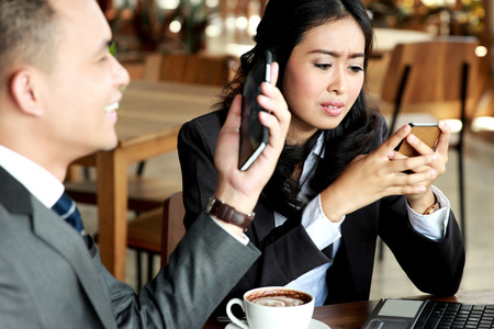 mobilephone: portrait of two business people look busy with their own mobilephone during coffee break