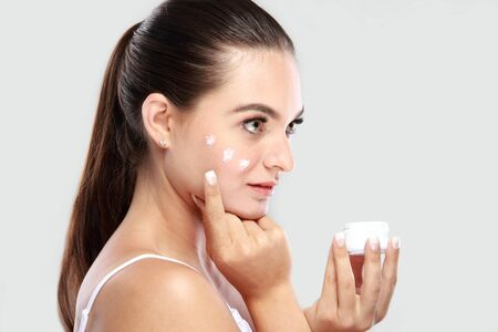 young add: side view of beautiful young woman applying some facial cream on her cheek with copy space Stock Photo