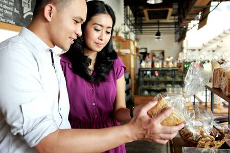 comparing: amazing young couple comparing bread at bakery shop
