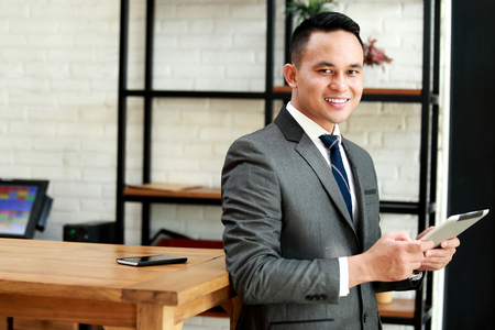 smiling businessman: young businessman smiling and holding a tablet while lean back at table