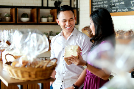 portrait of happiness of young couple shopping at bakery shop