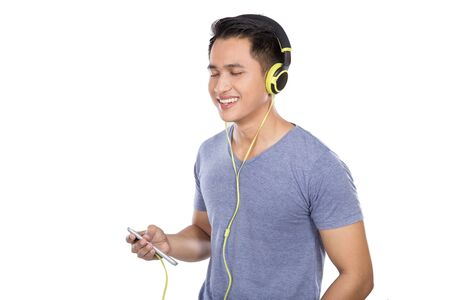 escuchando musica: Un retrato del hombre asiático joven que escucha la música con un auricular