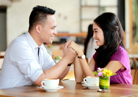 couple dating: portrait of romantic couple holding each other hands when dating at cafe Stock Photo