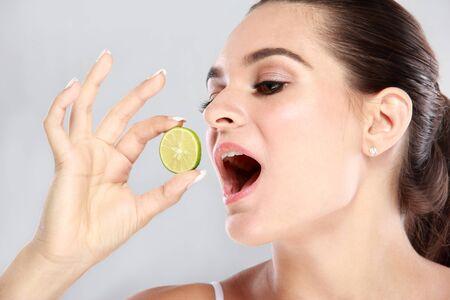 comiendo frutas: retrato de la hermosa mujer caucásica tratando de comer una rodaja de limón