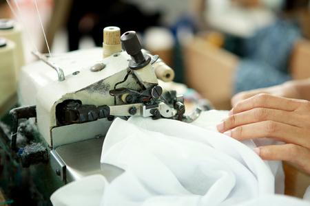 coser: retrato de la máquina de coser industrial y prenda de ropa en la fábrica textil