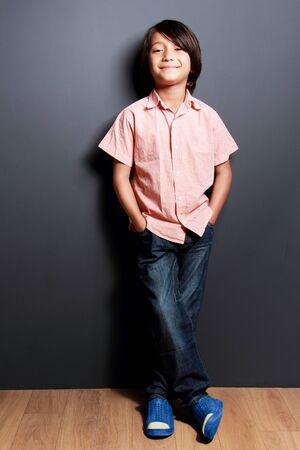 long pants: full body portrait of handsome little boy smiling with hands in his pockets