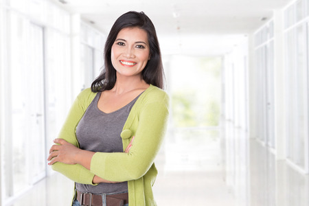 A portrait of middle age Asian woman smiling to the camera, looking happy. Stock Photo