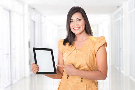 beautiful mature woman: A portrait of an asian woman holding a digital touch screen tablet computer presenting