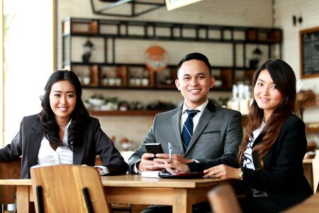 group of business people smiling and looking at camera while meeting at cafe Stock Photo