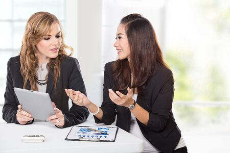 asian businesswoman: A portrait of a two young businesswoman wtih a tablet negotiating Stock Photo