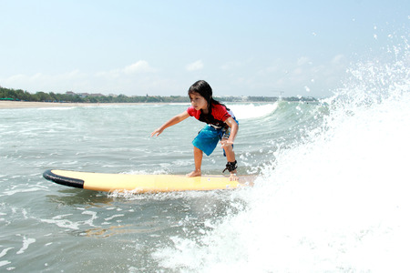 portrait of yooung boy learn to surf at ocean with splashing water