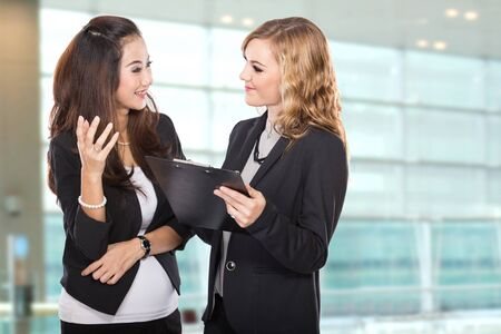 chatting: A portrait of a two young businesswoman wtih a clipboard discussing Stock Photo