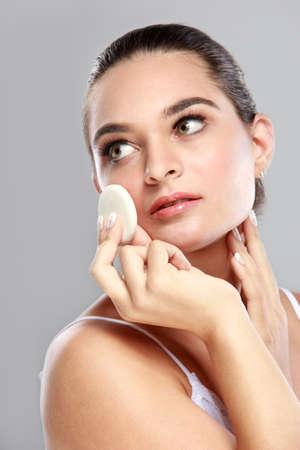 powder puff: portrait of beautiful young model applying some powder using powder puff