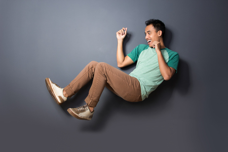 levitating: portrait of young man floating and act like fall over isolated on dark background
